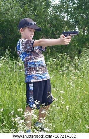 The boy shoots from a pistol - stock photo