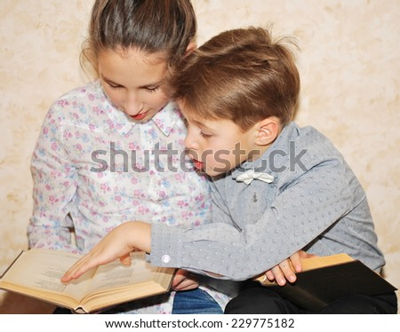 the boy shows something in the book girl - stock photo