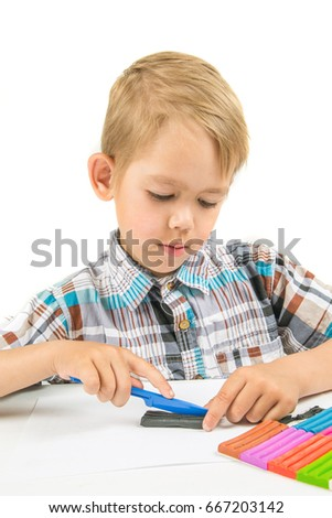 the boy sits at the table and sculpts from plasticine crafts on a white background