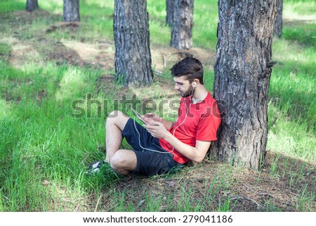 The boy sits under a tree and reads the book - stock photo