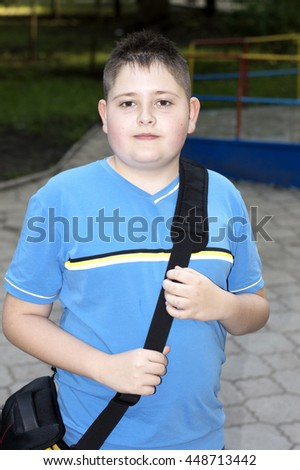 the boy with a bag in a blue t-shirt against park, a subject children