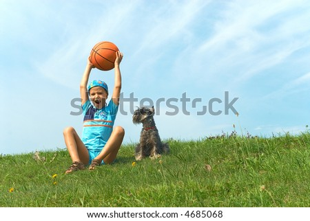 The boy with a basketball ball and dog on green grass - stock photo