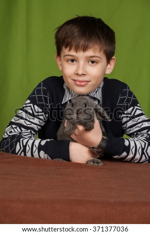 the boy with a gray rabbit on hands