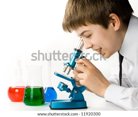 The boy with a microscope and various colorful flasks on a white background - stock photo