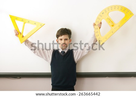The boy with angle and protractor at electronic board in school - stock photo