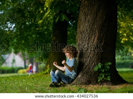 The boy with earphones in ears sits under a big tree. Something has excited him. The boy has clenched fists. On a face indignation. - stock photo