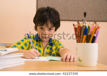 The boy with write-book and pencil in the classroom - stock photo
