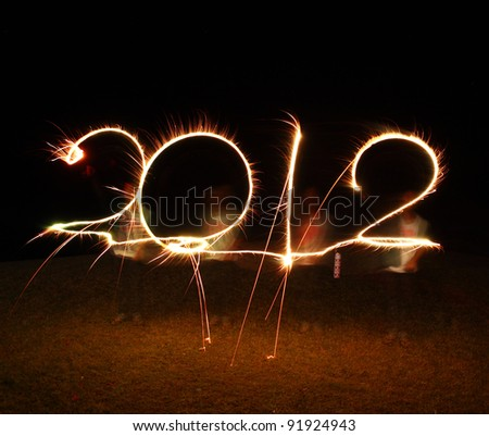 the boy write 2012 new year (fires) - stock photo