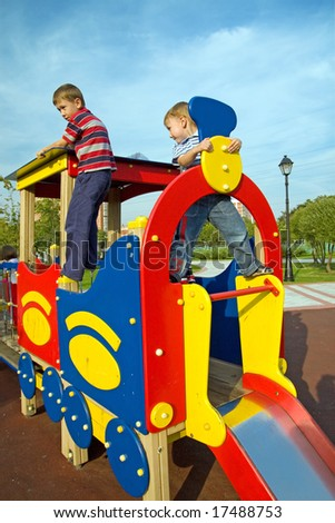 The boys climb on the equipment of a playground - stock photo