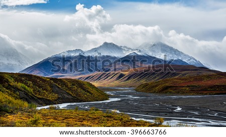 The braided channels of the Toklat river meanders through colorful Autumn foliage in Denali National Park, Alaska. - stock photo