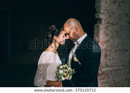 the bride and groom are holding a bouquet of white flowers and greenery in the background Vintage wall of white brick - stock photo