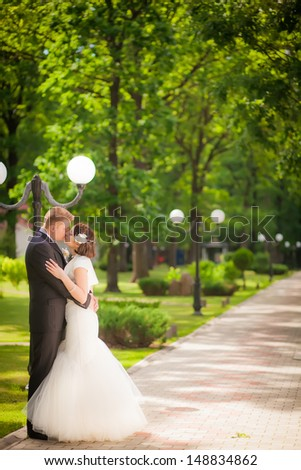 the bride and groom are walking outdoors in park - stock photo