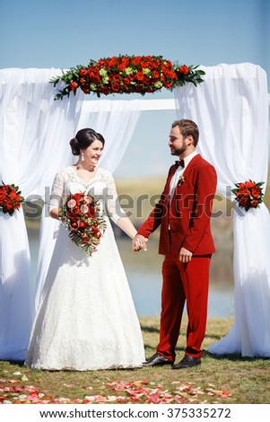 The bride and groom during a wedding ceremony on the background of an arch of red flowers and white fabric, outdoors, on the banks of the river. Marsala color and decoration style. - stock photo