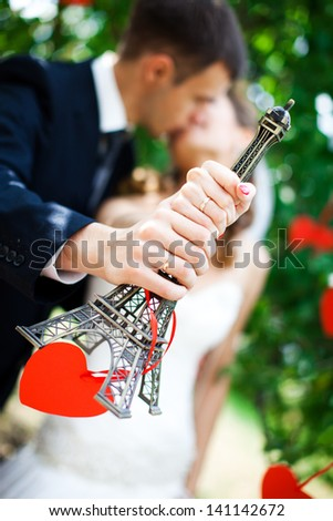 the bride and groom hold a miniature Eiffel Tower - stock photo
