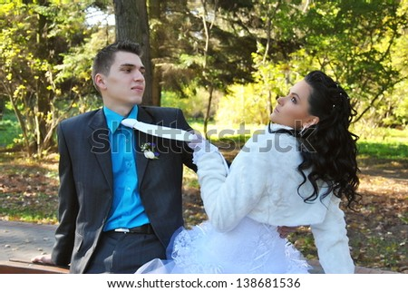 The bride and groom in a park in autumn