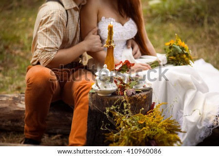 The bride and groom in autumn forest. Decorated wedding. Rustic. Wedding decor, wildflowers, bouquet, table setting, candle. - stock photo