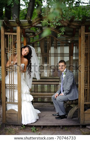the bride and groom in the gazebo in the park - stock photo