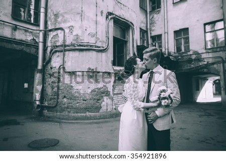 The bride and groom kiss in the courtyard of old buildings