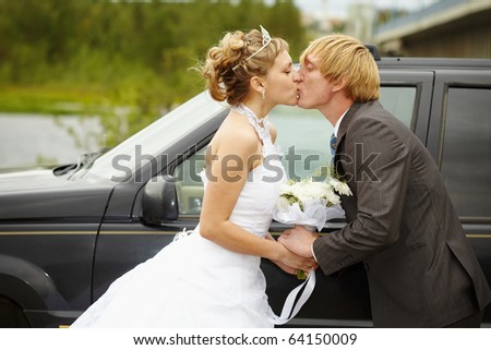 The bride and groom kissing near a black car - stock photo
