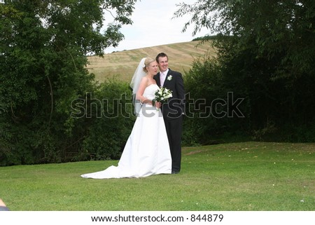 The bride and groom pose after the wedding - stock photo