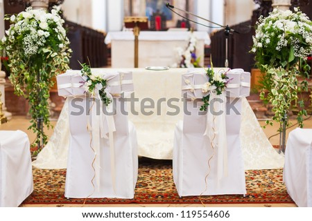 The bride and groom's chairs inside of the church. - stock photo
