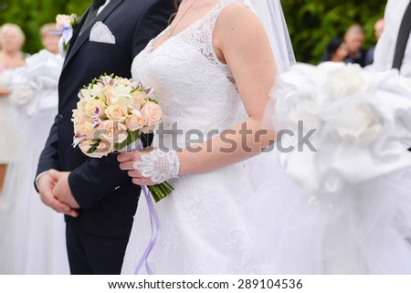 the bride and groom with a bouquet and holding hands each other - stock photo