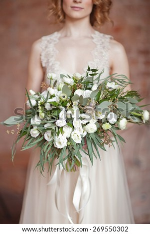 the bride holding wedding bouquet of white ranunculus, grass and roses - stock photo