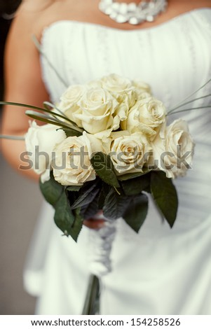 the bride holds a wedding bouquet from white roses