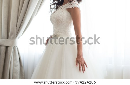 The bride in a white dress standing in front of a window near the curtains