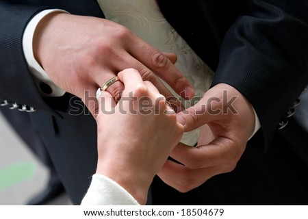 The bride puts on a wedding ring to finger of the beloved - stock photo