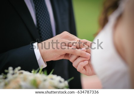The bride puts the ring on the finger of the groom