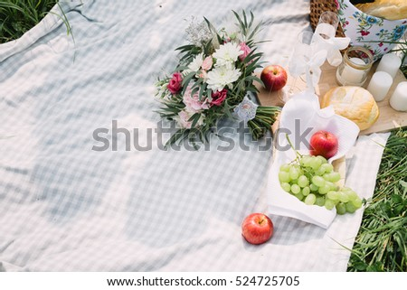 the bride's bouquet and fruit lying on the picnic blanket