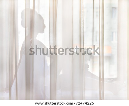 The bride sat on the window sill behind the curtains - stock photo