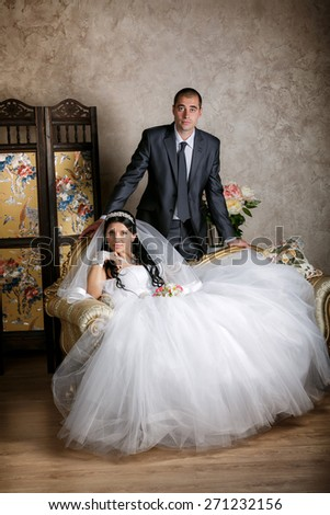 The bride sits in a chair and the groom stands near groom in the room with a beautiful interior - stock photo