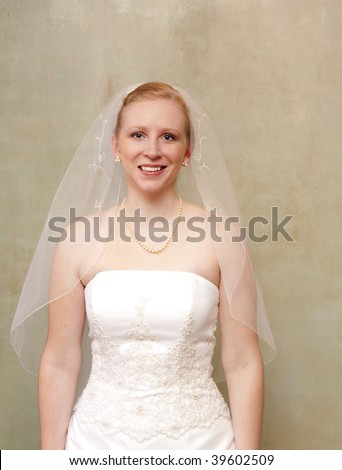 The bride smiling and radiant in her white wedding gown - stock photo