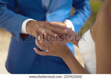 The bride wears a wedding ring on the groom. Closeup photo - stock photo