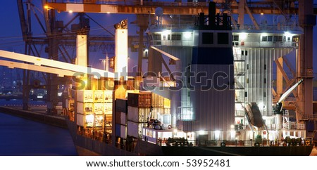 The bridge of a big container ship being loaded at dusk at an industrial harbor