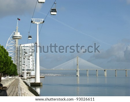 The bridge over the river tagus the observation tower Vasco da Gama and a cable car in Lisbon in Portugal - stock photo