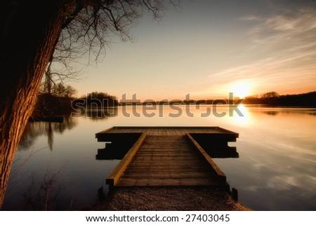 The bridge to the lake under the sunset - stock photo