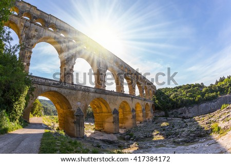 The bridge was built in Roman times on the river Gardon. Three-tiered aqueduct Pont du Gard - the highest in Europe. Provence, setting sun shines in sky - stock photo