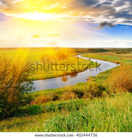 The bright evening sun over the river and green meadows - stock photo