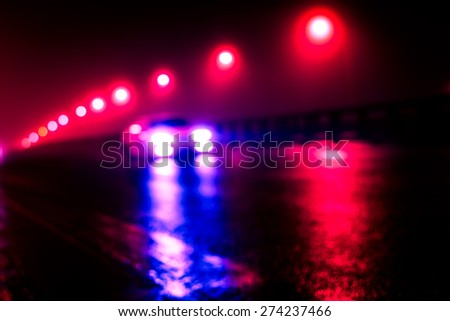 The bright lights of the city at night, the car racing on the road bridge. Defocused image, image in the red-blue toning