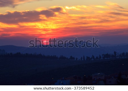 The bright red gold sunset in the hills over a village - stock photo