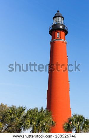 The brilliant red lighthouse at Florida's Ponce de Leon Inlet (formerly Mosquito Inlet) has stood watch over the Atlantic Ocean since 1887. - stock photo