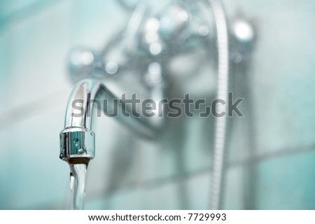 The brilliant water faucet in a bathroom - stock photo