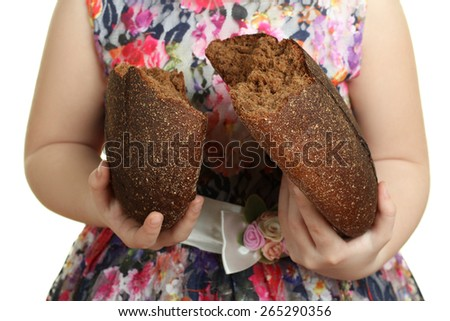 the broken bread in half in the hands of a little girl - stock photo