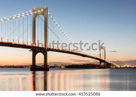 The Bronx-Whitestone Bridge reflecting on the East River at night in New York. - stock photo