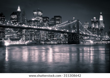 The Brooklyn Bridge against the Manhattan skyline in the early evening. - stock photo