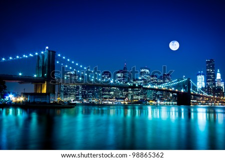 The Brooklyn Bridge lit up at night and the downtown Manhattan skyline under a full moon - stock photo