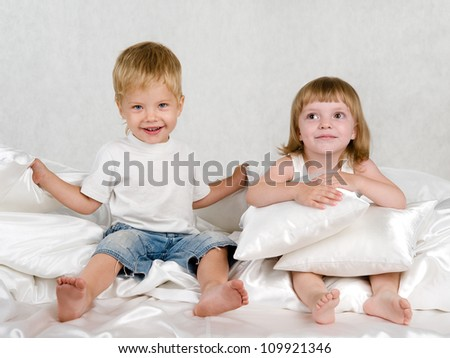 the brother and the sister sit on a bed - stock photo